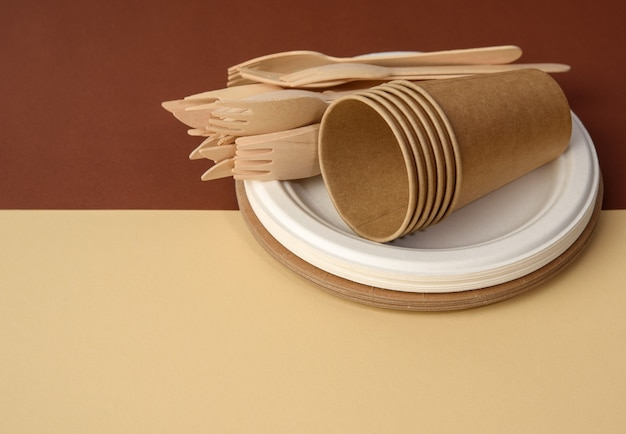 Paper cup and wooden fork, empty round brown disposable plate made from recycled materials on a brown surface. concept of the absence of non-recyclable garbage, rejection of plastic