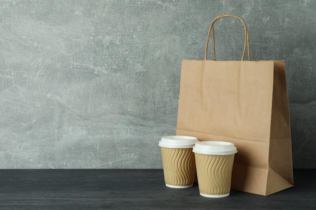 Бумажные стаканчики и сумка на темном деревянном столе