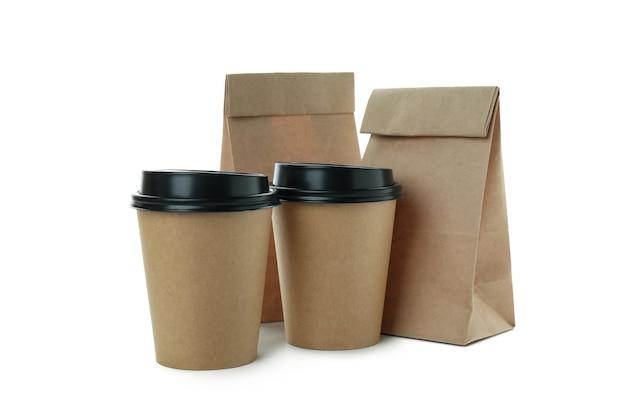 Бумажные стаканчики и бумажные пакеты, изолированные на белой поверхности