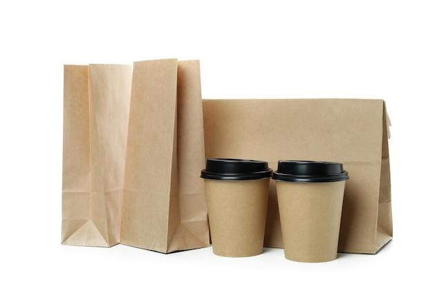 Бумажные стаканчики и бумажные пакеты, изолированные на белом фоне