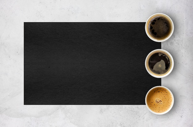 Paper cups of coffee on cement table background. top view