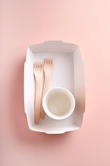 종이컵, 접시, 가방, 나무 포크, 빨대, 패스트푸드 용기, 분홍색 배경의 나무 칼. 에코크래프트 종이 식기. 재활용 및 음식 배달 개념입니다. 조롱. 평면도