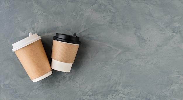 コピースペースのある上面から見た灰色の壁にコーヒーや紅茶用の紙コップ。フラットレイテイクアウトコーヒーまたはホットドリンク。最小限の詳細を備えたレイアウト