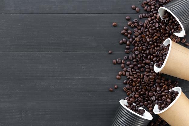 Бумажные стаканчики кофе и бобов на черном фоне деревянные. вид сверху