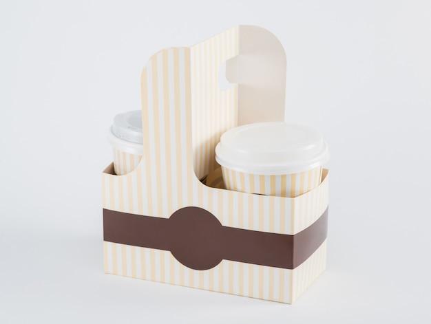 Бумажные стаканчики с кофе в коробке на вынос на белом фоне