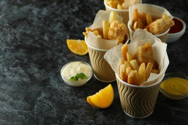 Бумажные стаканчики с жареной рыбой и жареным картофелем