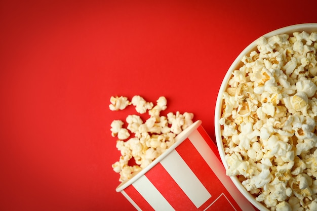 Paper cups with popcorn on red background.