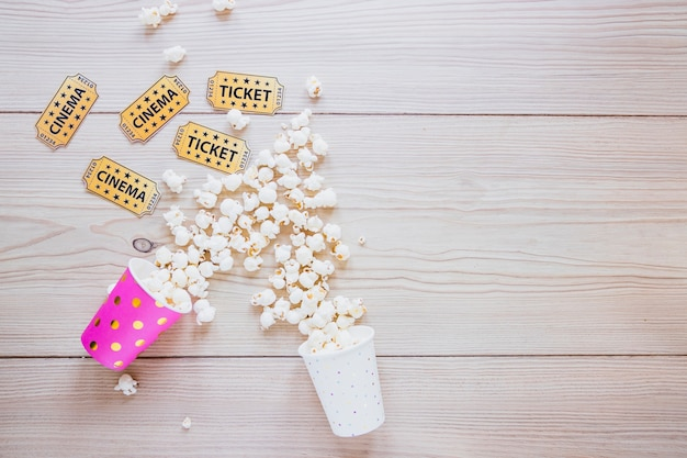 Paper cups with popcorn and tickets