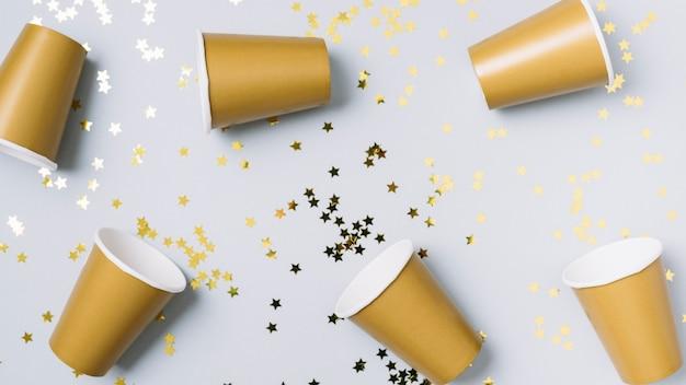 Bicchieri di carta con lustrini sul tavolo