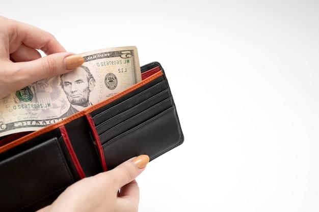 女性の手で財布の紙幣。女性は財布からドルのお金を取り出します。