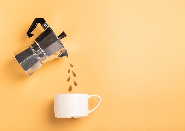 Paper cut drops pouring from a geyser coffee maker into a cup on yellow paper background. coffee preparation concept. top view, flat lay. minimalist design. space for text.