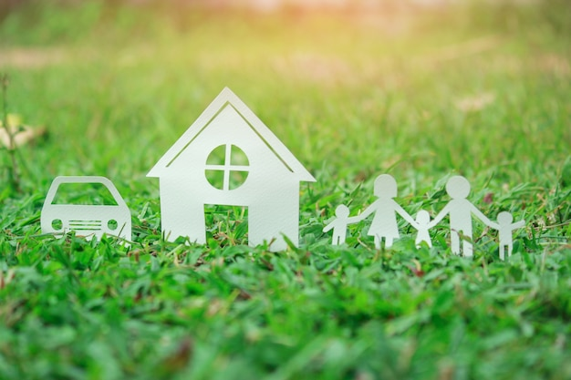 Paper cut of family on green grass, concepts saving money for house and car