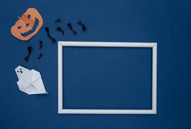 종이 컷 비행 박쥐와 할로윈 호박, 텍스트에 대한 흰색 프레임과 고전적인 파란색 배경에 유령. 할로윈 배경입니다. 공간을 복사합니다. 평면도