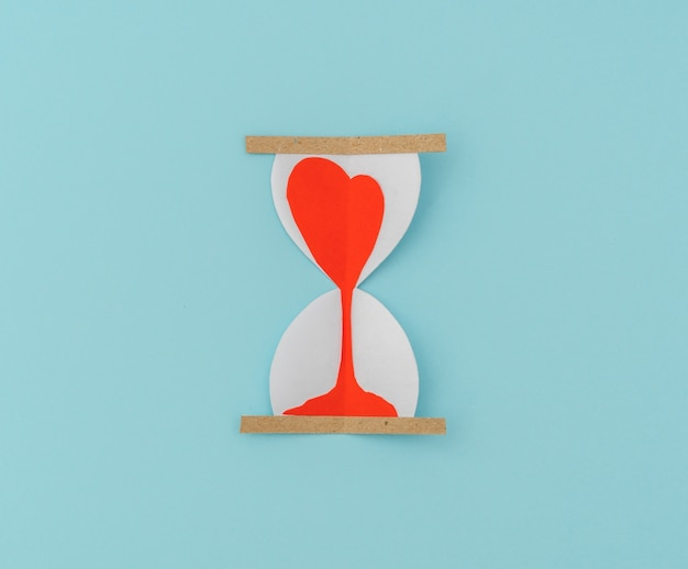 Paper cut of hearts in sand clock .