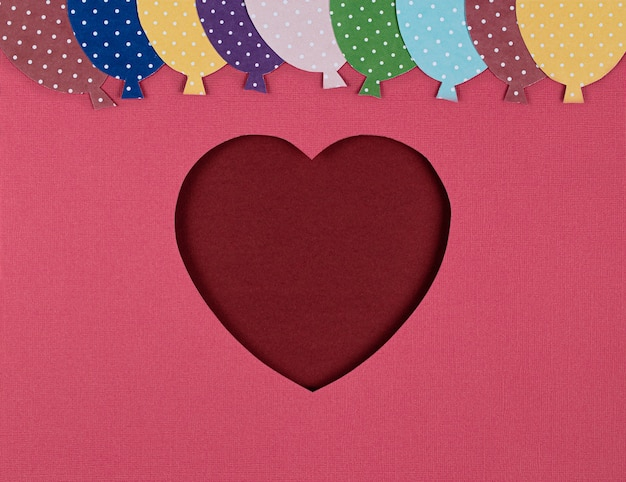 ピンクの背景に赤いハートと風船の形にカットされた紙。バレンタインデーカード、切り絵。