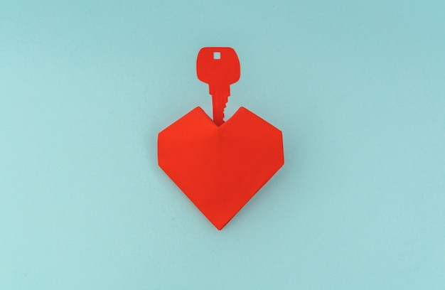 Paper cut of key for heart as a symbol of love .