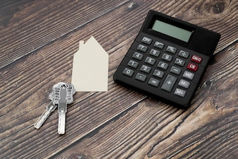 Paper cut out house with keys and calculator on wooden textured surface