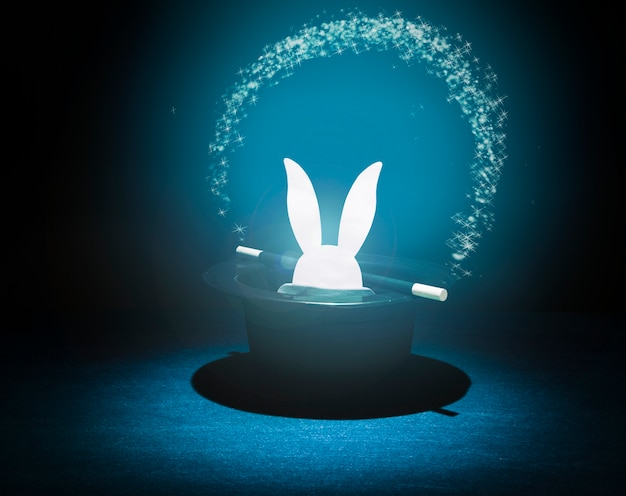 Paper cut out rabbit heads in the top black hat with glowing star arch