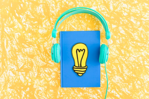 Paper cut out yellow light bulb on closed notebook with headphone on textured background