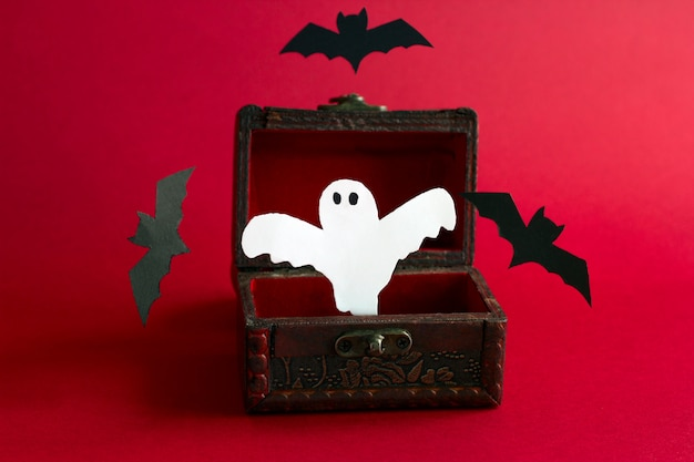 Paper cut scary ghost and bats fly out of an old vintage wooden chest