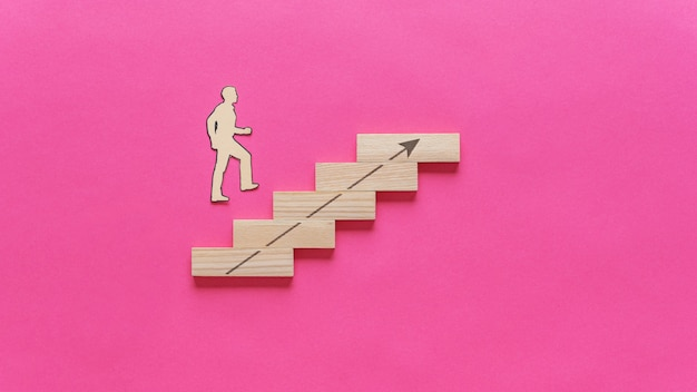 Paper cut silhouette of a businessman walking up the stairs made of wooden pegs with arrow pointing upwards.
