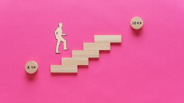 2019年から2020年にかけて、木製のペグで作られた階段を上る男の切り絵のシルエット。