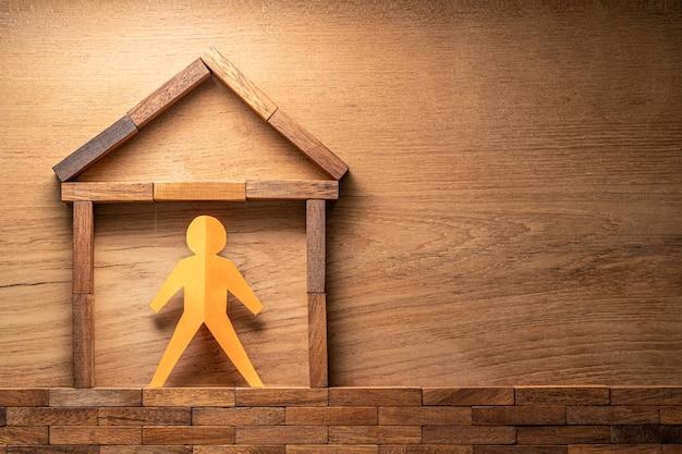 木製の壁に家を作った木製のブロックの紙の切り抜き人間の姿