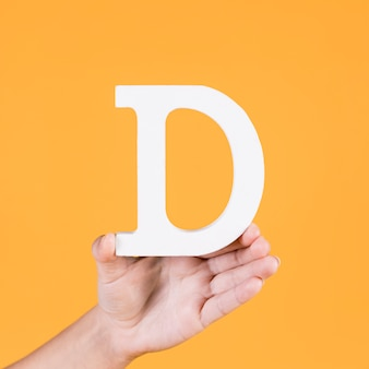 Paper cutout of letter d hold by human hand on yellow backdrop