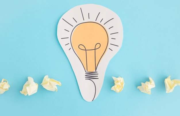 Paper cutout of light bulb with crumpled paper on blue background