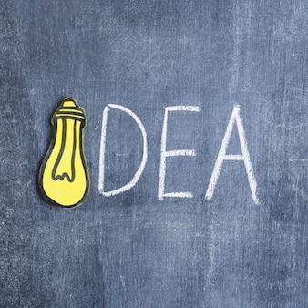 紙の切り抜き黄色の電球は、黒板にテキストのアイデアを作る