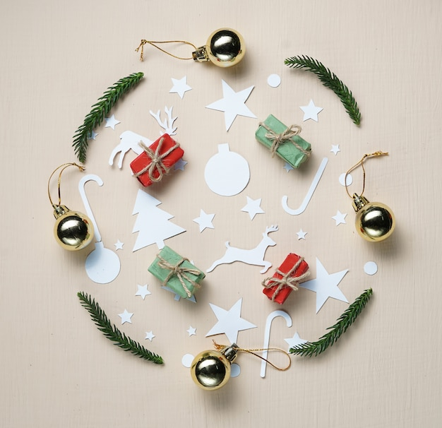 Paper cutting and christmas ornament forming circle on beige background