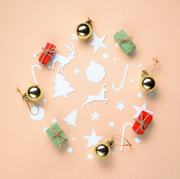Paper cutting and christmas ornament forming circle on peach background