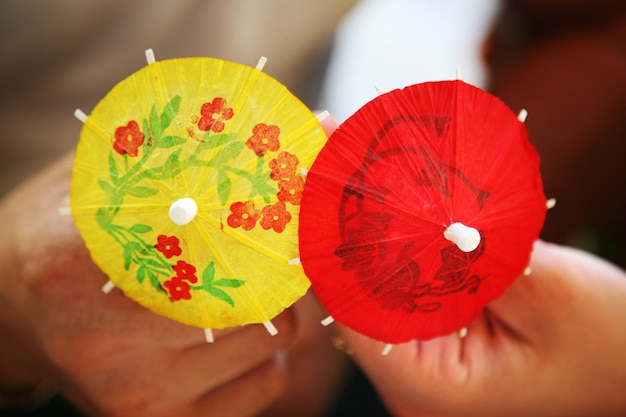 Paper decorative umbrellas in hands