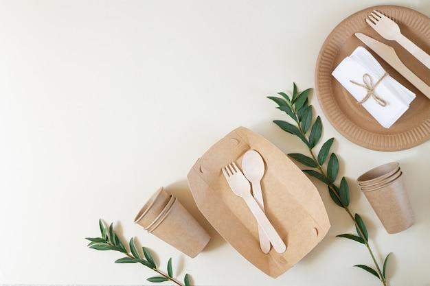 Бумажная одноразовая тарелка, чашки, коробка, салфетки и деревянные столовые приборы, вид сверху. экологичная упаковка на бежевом фоне с копией пространства.