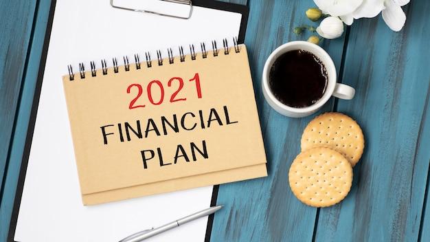 '2021 년 재정 계획'이 적힌 종이 문서와 일기 및 커피 한 잔