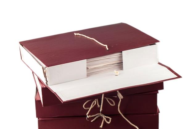 白い背景で隔離のアーカイブに積み上げられた紙の文書