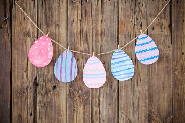 Paper easter painted eggs painted hang on clothespins on background
