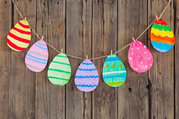 ペーパーイースター塗装卵は背景の古い木製の壁の洗濯はさみに掛ける。