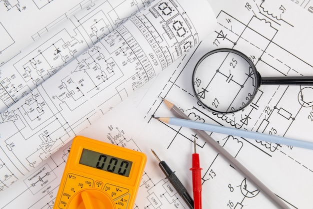 Paper electrical engineering drawings, pencil, magnifying glass and digital multimeter