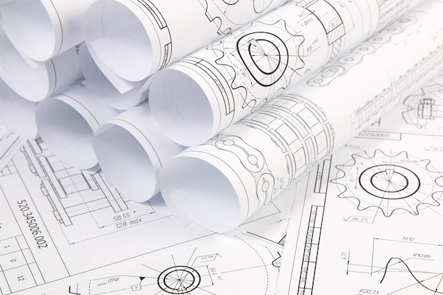 Paper engineering drawings of industrial parts and mechanisms