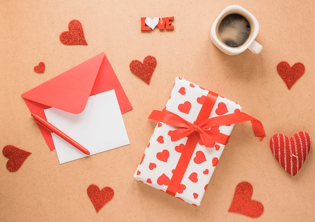 Paper on envelope near pen, present, cup of drink and ornament hearts