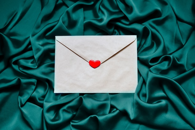 직물 배경에 붉은 마음으로 종이 봉투