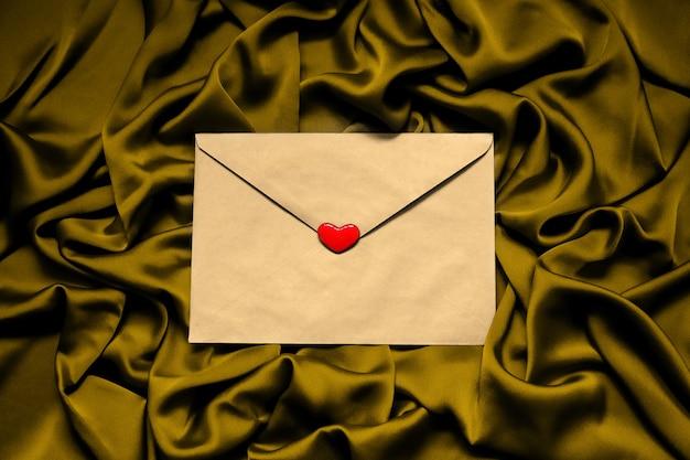 Бумажный конверт с красным сердцем на тканевом золотом фоне