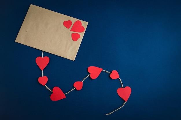 コードで飾られた赤い紙のハートの平らな紙の封筒は、コピースペースと紺色の背景に横たわっていた