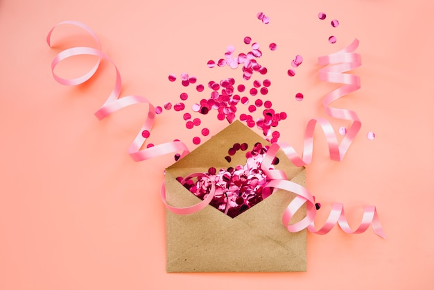Paper envelope with pink confetti and ribbons