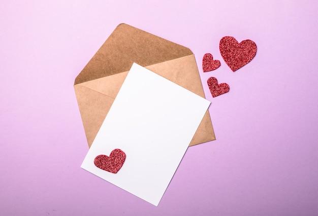 Бумажный конверт с сердечками валентинок на фиолетовом фоне. плоская планировка, вид сверху. романтическое любовное письмо для концепции дня святого валентина.