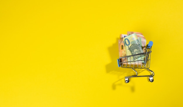 Paper euro bills in a miniature metal cart on a yellow surface, view from above, copy space