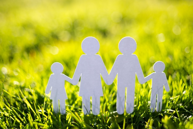Paper family on green grass background