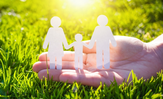 Paper family in hand on green grass background