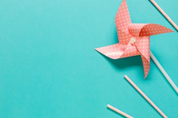 Бумажный веер и соломинки на цветной поверхности